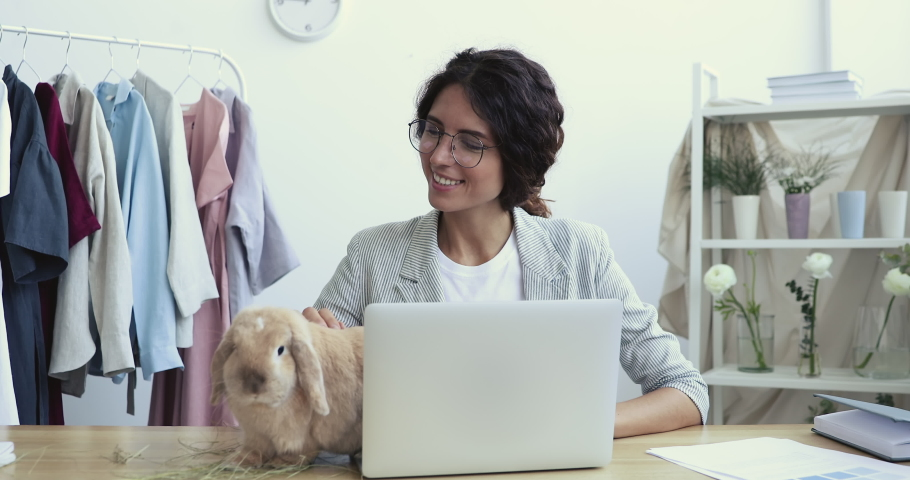 Smiling young female entrepreneur stroking small cute domestic bunny, jumping on table in modern studio atelier. Happy beautiful designer in glasses playing with funny rabbit during workday in office.