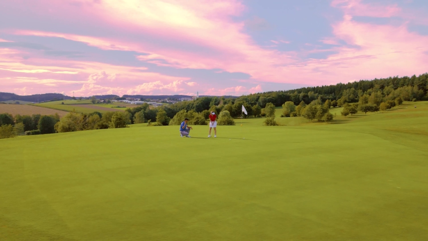 Orbit around woman and golf pro putting on the golf green under red sky