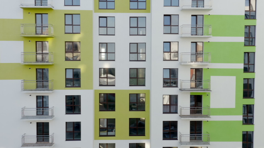 Tilt up view of contemporary apartment building with large windows and colorful walls of the facade of a new house for city residents, or offices with a beautiful modern facade in the early summer - | Shutterstock HD Video #1057833184