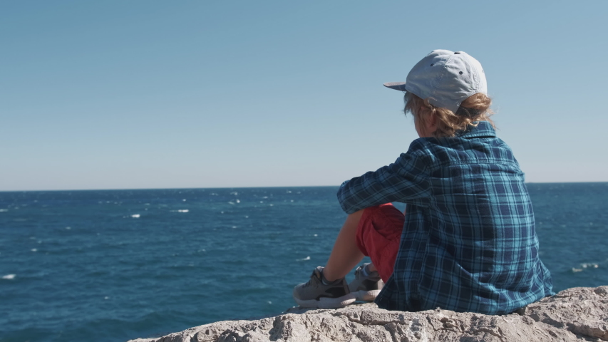 Child sitting on the top of the mountain and watching sea waves. Boy on the cliff enjoying nature landscape on blue sea background. Summer vacation, tourism, healthy lifestyle concept