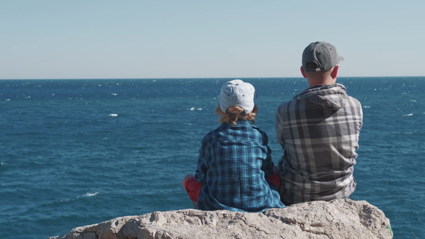 Father and son sitting on top of mountain and watching sea waves. Boy and man on cliff enjoying nature landscape. Togetherness, friendship, childhood, parenthood, man support concept