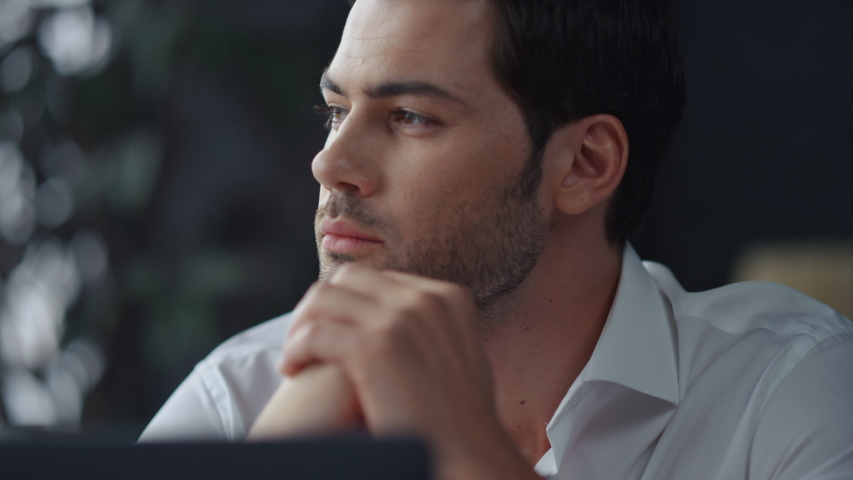 Thoughtful businessman sitting at remote workplace with laptop computer. Pensive professional thinking at table in office. Focused business man face looking around. Serious man portrait Royalty-Free Stock Footage #1057837675