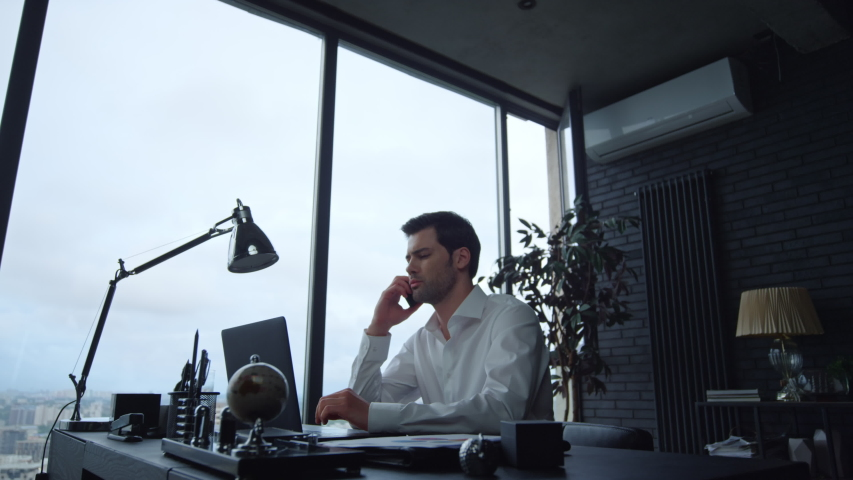 Focused businessman working on laptop computer in office interior. Male worker answering on phone call. Man talking smartphone at remote workplace. Business man calling phone at office