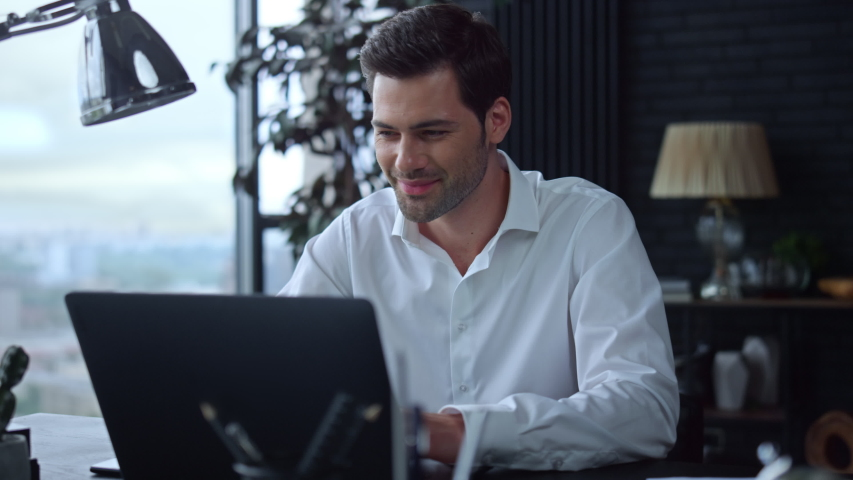 Smiling businessman working on laptop computer at home office. Male professional typing on laptop keyboard at office workplace. Portrait of positive business man looking at laptop screen indoors