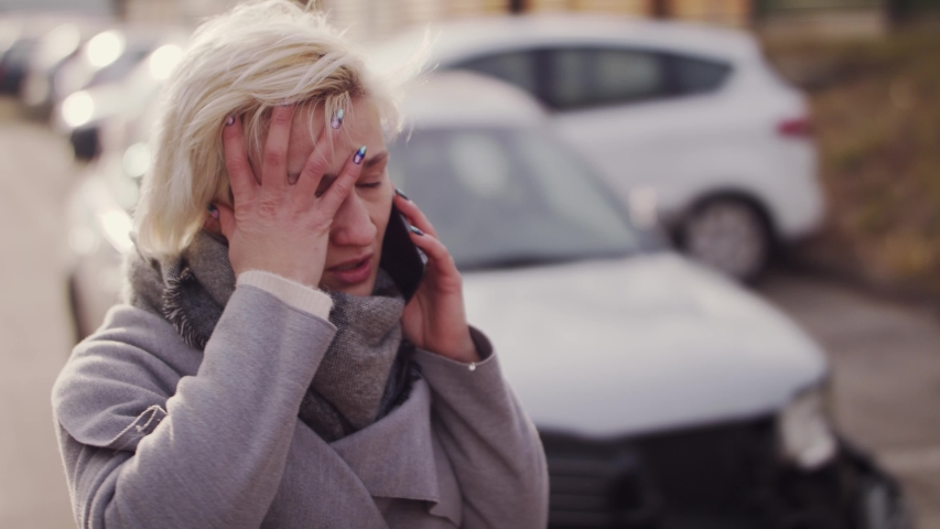 Young frustrated blonde woman making a phone call after a car accident.