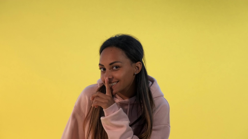 Beautiful mixed-race woman making a hush gesture on yellow background. It must be quite there. | Shutterstock HD Video #1057839388