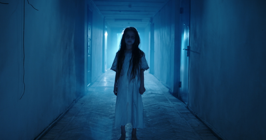 Little girl in white dress looking like a ghost carelessly dancing in the hallway of a haunted house - halloween costume party, horror movie 4k footage   Shutterstock HD Video #1057842181