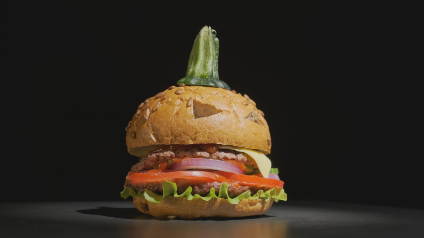 Halloween beef burger in shape of pumpkin rotating on black background. halloween party dish. | Shutterstock HD Video #1057842715