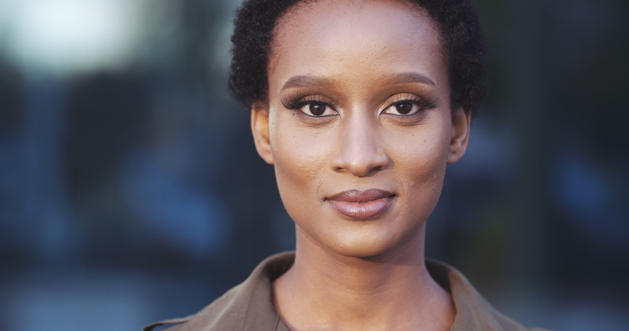 Front closeup portrait of young mixed race beauty African American black woman with short hair afro style standing on street, looking friendly at camera. Human face, ideal natural make up skin concept | Shutterstock HD Video #1057846054