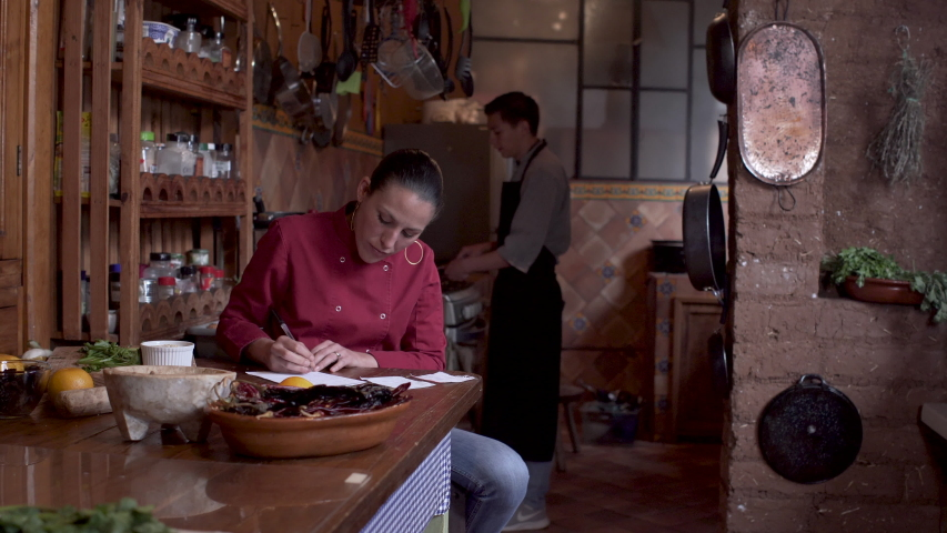 Woman chef writing with a pen and paper in a restaurant kitchen while a Latino man cooks on a stove behind her- push in