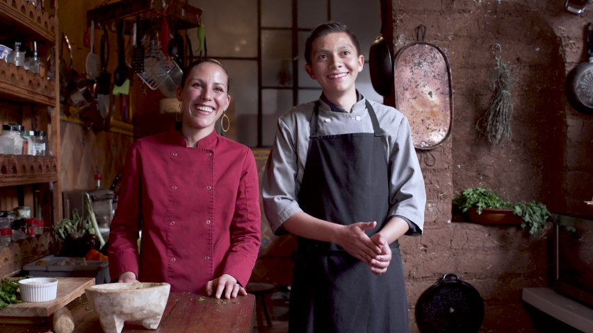 Latino male and female restaurant workers wearing a chefs coat and apron laughing and having a good time in a rustic kitchen filled with herbs and spices