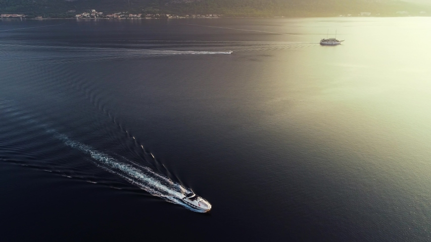 Aerial cinematic view of sailing speedboat, yacht and sailboat. Sunset above the sea in Italy, Monaco, France, Ibiza, Croatia, Greece or Fort Lauderdale. Luxury lifestyle in summer season   Shutterstock HD Video #1057856335