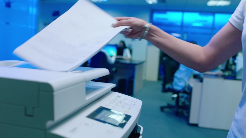Woman using printer or scanner in office . Office worker use print machine on blurred office background with workers and computers . Hand take papers and press buttons on multifunctional copier .