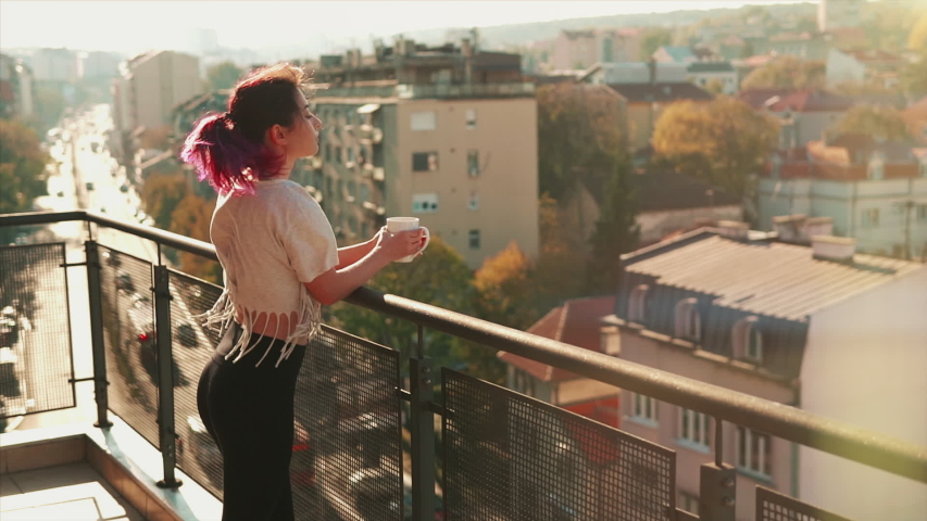 Gorgeous young woman with purple hair stays on balcony holds cup of hot coffee or tea watching a beautiful urban view and then close eyes and enjoy relax breathing fresh freezing air of spring | Shutterstock HD Video #1057863139