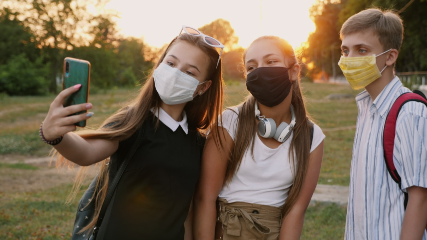 Teenagers with backpacks and wearing protective masks on their faces take a selfie on a smartphone in a city park at sunset Royalty-Free Stock Footage #1057863961