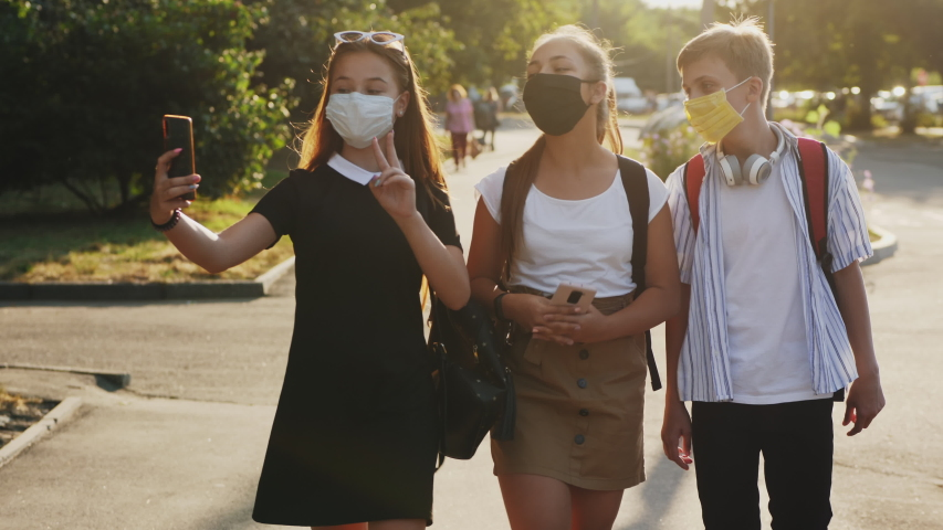Three school-age friends wearing protective masks and backpacks are walking down the street, taking selfies, talking and laughing Royalty-Free Stock Footage #1057863967
