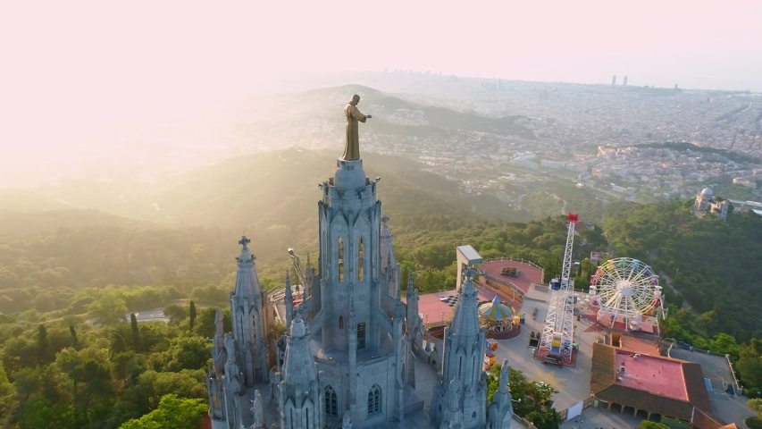Fantastic overview aerial footage around the Expiatory Church of the Sacred Heart of Jesus (Temple Expiatori del Sagrat Cor) at the dawn in Tibidabo mountain in Barcelona. Royalty-Free Stock Footage #1057865725