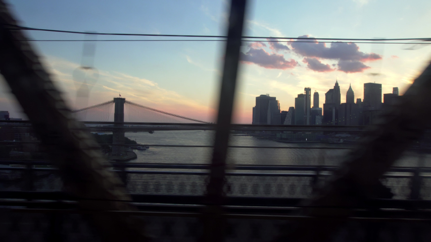 Crossing Manhattan Bridge on the Q train, sunset view over downtown New York and Brooklyn Bridge. Train Crossing. | Shutterstock HD Video #1057868320