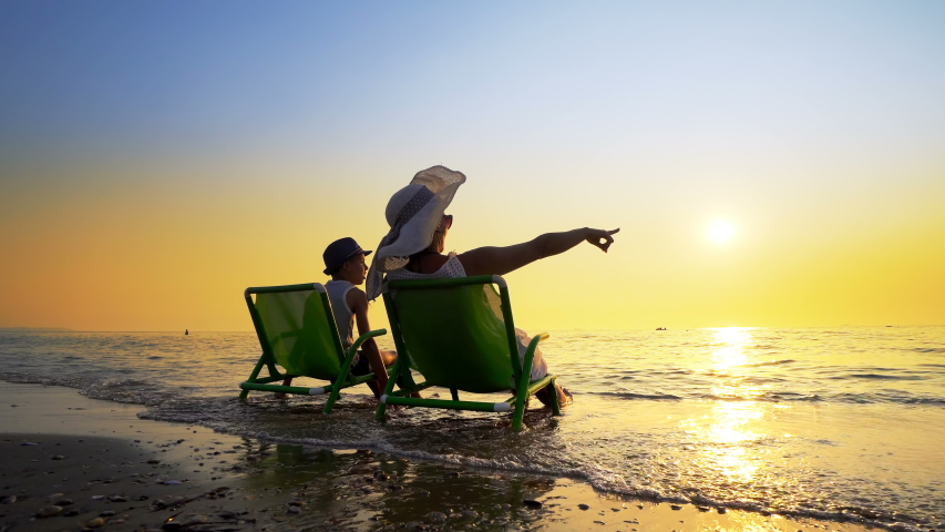 Happy family enjoy luxury sunset on the beach during summer vacations. Mother and son are sitting on a beach deck chair, against sunset, cinematic steadicam shot Royalty-Free Stock Footage #1057870630