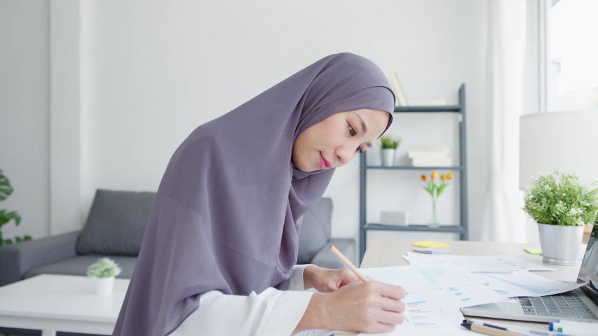 Beautiful Asia muslim lady in headscarf casual wear using laptop in living room at house. Remotely working from home, new normal lifestyle, social distancing, quarantine for corona virus prevention. Royalty-Free Stock Footage #1057873579