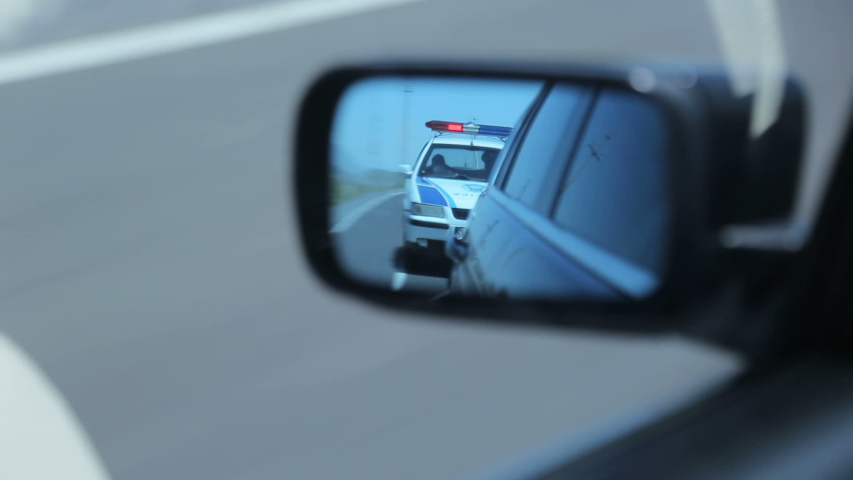 Police car in the side mirror chasing a car on highway. Police chase, the car is running away from the chase Royalty-Free Stock Footage #1057875790