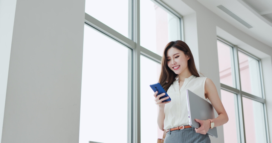 asian young businesswoman use smart phone with laptop on her business trip Royalty-Free Stock Footage #1057878100