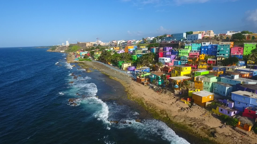 Drone flying above La Perla neighborhood in San Juan Puerto Rico during summer season. Colorful houses close to the beach beautiful paintings sea waves splashing
