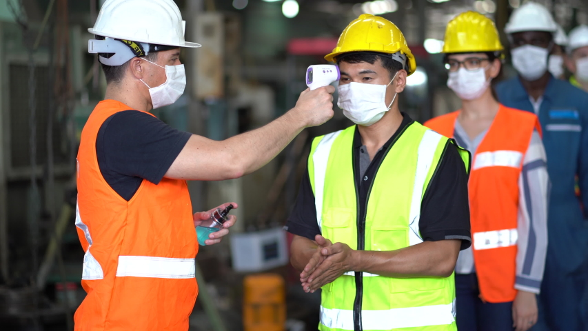 Head of industrial plant  using thermometer to check body temperatures Before going to work  COVID-19 prevention policy | Shutterstock HD Video #1057882240