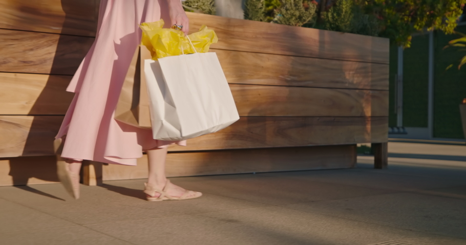 Woman in pink dress with shopping bags walking in a city at sunset. Slow motion of female in stylish outfit is walking by the outdoor shopping mall on sunny summer evening. Malibu, California, USA