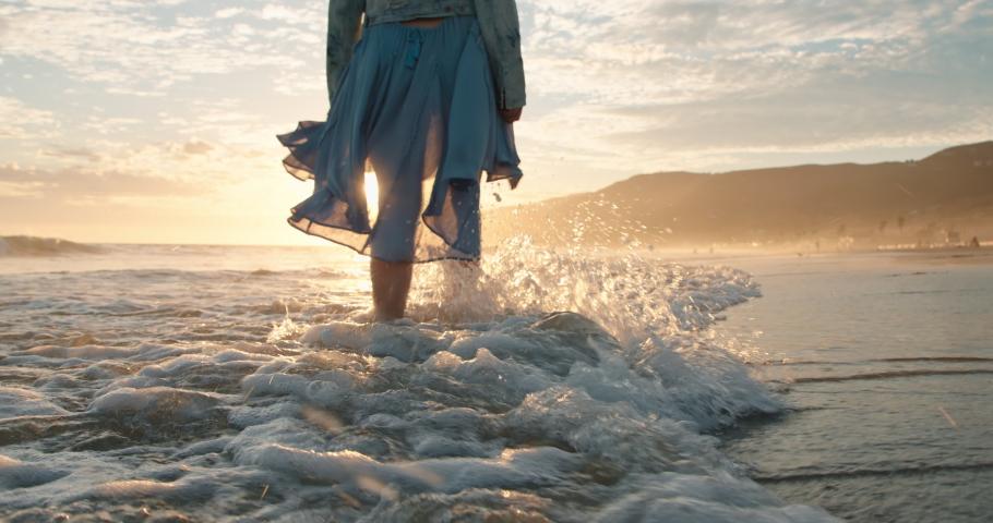 Slow motion woman walking barefoot in ocean waves in golden sunset light. Cinematic 4K of happy female traveler enjoying her summer vacation in Malibu, California, USA. Woman in beautiful waving dress