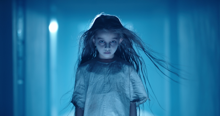 Little caucasian girl in ghost white sundress costume for halloween roaring into camera, frightening someone in hallway of haunted house 4k footage | Shutterstock HD Video #1057888408