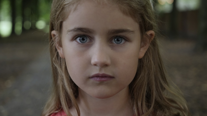 Portrait Little Child Girl Looking at Camera Standing on Street in City on Summer Day. Young Sad Thinking Curiosity Child Looking at Camera Closeup Outdoors. Face Eyes Serious Contemplative Child. Royalty-Free Stock Footage #1057890076