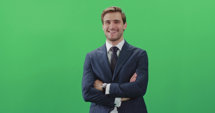 Businessman in a suit standing in green room and looks at the camera, chroma key background, a man smiles, positive emotions.