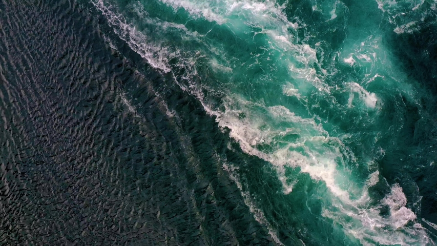 Waves of water of the river and the sea meet each other during high tide and low tide. Whirlpools of the maelstrom of Saltstraumen, Nordland, Norway | Shutterstock HD Video #1057895884