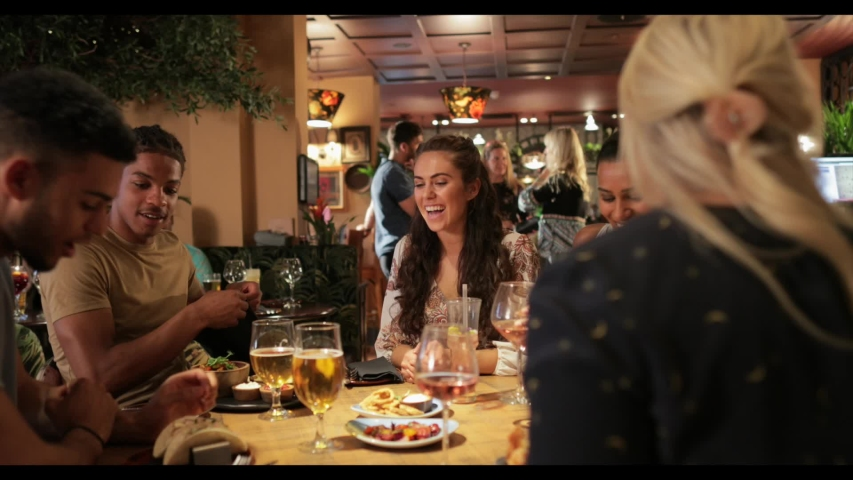 A group of friends out for a meal together, they are being served by a waitress. They then share some nachos.    Shutterstock HD Video #1057896139