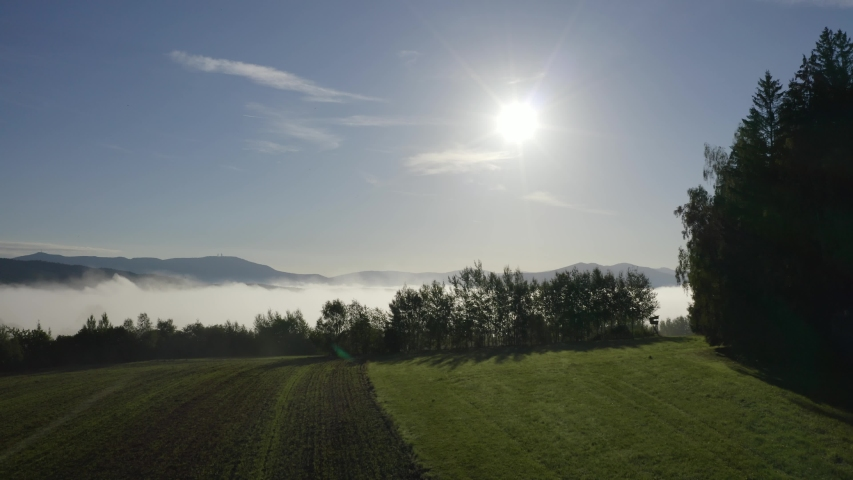 Camera flying towards the sun over fields of fog over late summer landscape, in the background the blue mountains of the Bavarian forest