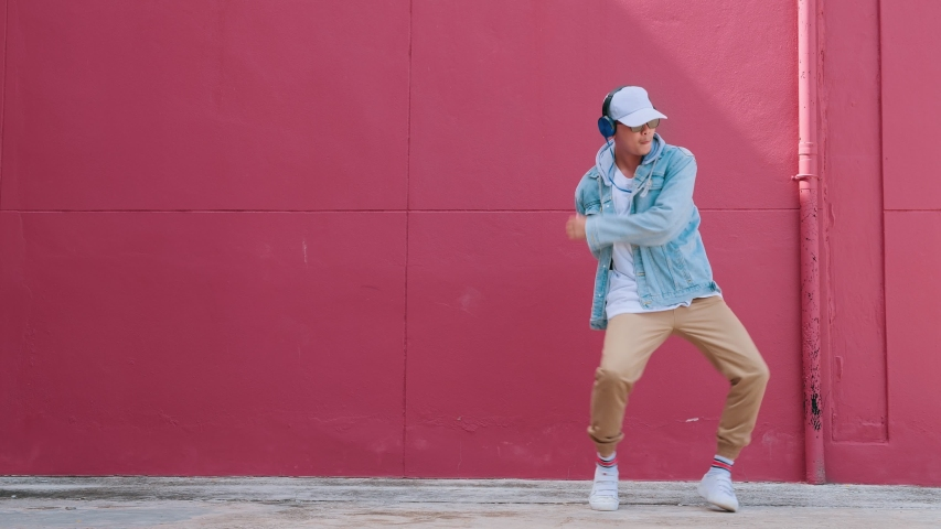 Dancing man with headphones listening to music performing various freestyle dance outdoors in street wall having fun. Modern lifestyle, happiness concept. breakdancing, hiphop dancing, street dancing. | Shutterstock HD Video #1057901770