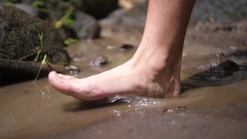 A slow motion clip of a male foot stepping into a dirty puddle of water with soft, muddy soil underneath it.