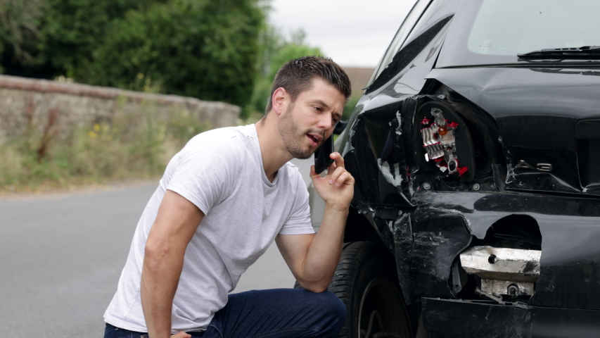 Unhappy Male Driver With Damaged Car After Accident Calling Insurance Company On Mobile Phone