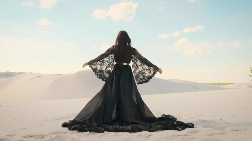 Beauty woman, rear view. Queen in black clothes dancing in desert. Girl fashion model. long silk arab dress. Back of luxury elegant goddess. backdrop white sand, blue sky. Mysterious silhouette queen Royalty-Free Stock Footage #1057909840