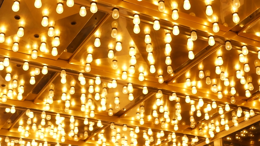 Old fasioned electric lamps blinking and glowing at night. Abstract close up of retro casino decoration shimmering in Las Vegas, USA. Illuminated vintage style bulbs glittering on Freemont street. | Shutterstock HD Video #1057912366