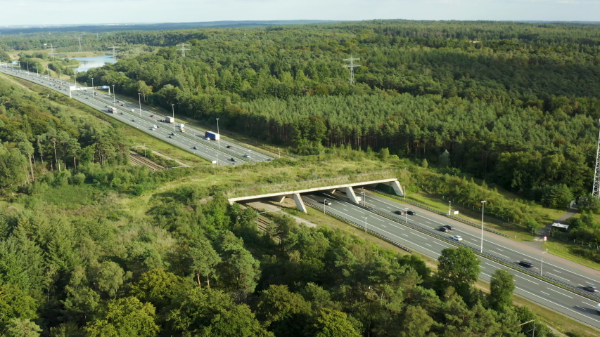 Aerial rising shot of an ecoduct, a wild life bridge that crosses a busy highway in the Netherlands   Shutterstock HD Video #1057918447