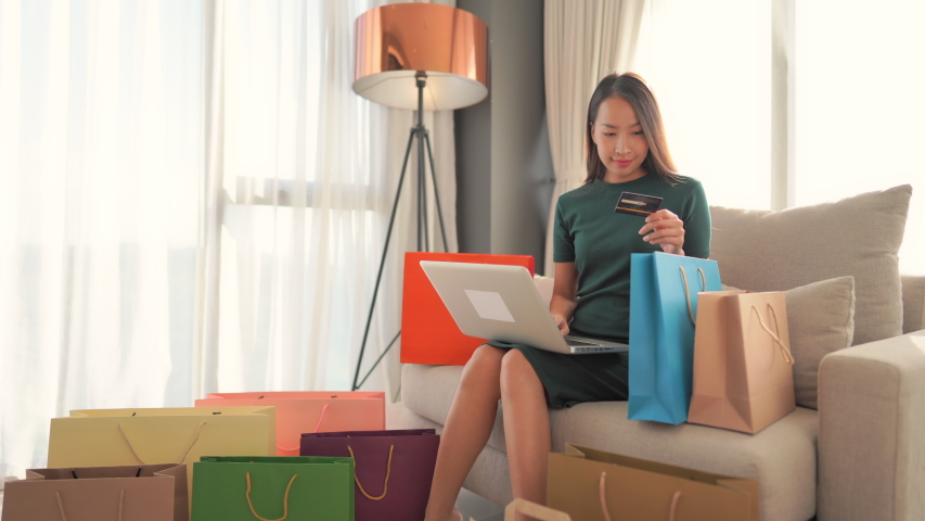 Close up asian woman relaxing home sofa using credit card buy shopping online. Spendthrift woman. Royalty-Free Stock Footage #1057920307