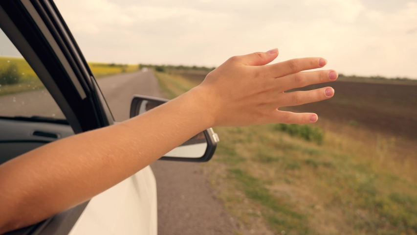 Girl hand in the car window. Girl travels with her family by car. Happy child travels. Happy family concept. Girl hand on the sun through the car window. Happy child in the car