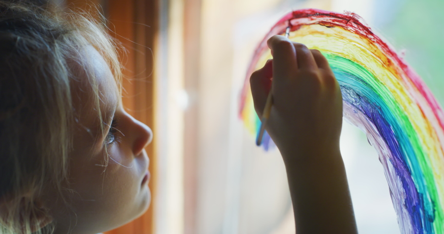 Authentic shot of a cute little creative happy smiling preschooler girl painter is drawing a rainbow on a glass of a window in a kitchen at home. Concept of happiness, arts, childhood, covid free Royalty-Free Stock Footage #1057929394