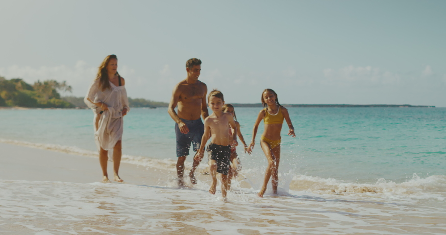 Happy young family playing and splashing on the beach with adorable golden retriever, family vacation lifestyle