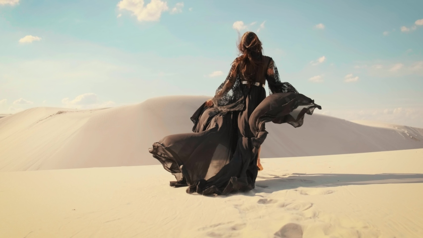 Silhouette of a happy woman running in the desert. Long black silk dress and hair flying fluttering in the wind in slow motion. A tourist is enjoying a vacation in the Dubai desert. Video footage 4K Royalty-Free Stock Footage #1057932925