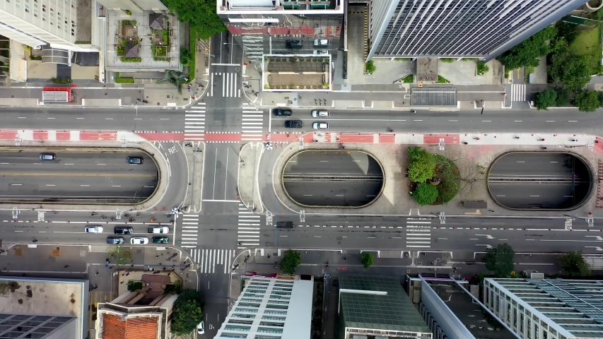 Top Down View of Intersection of famous avenues in Brazil. Paulista  and Consolacao Avenues. Transportation Scene. Aerial View of Traffic and Pedestrian on Crosswalk. Aerial Landscape of Sao Paulo Royalty-Free Stock Footage #1057933528