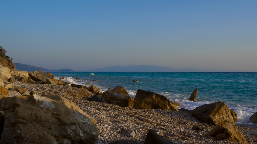 Sea waves splashing on rocks of peaceful beach with pebbles, seascape with Corfu island in background   Shutterstock HD Video #1057939090