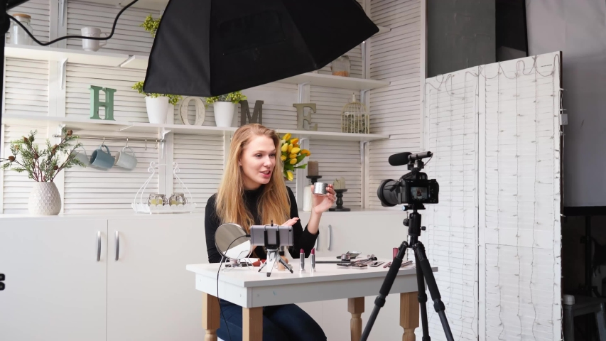 Beauty blogger woman filming daily makeup routine tutorial at camera on tripod. Influencer lady live streaming cosmetics product review in home studio. Vlogger female applies skin powder with brush. | Shutterstock HD Video #1057942762